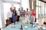 rodzina z para młodą pozują do zdjęcia na sali weselnej